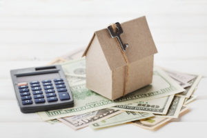 Model of cardboard house with key, calculator and cash dollars. House building, loan, real estate. Cost of public utilities, insurance, rent or buying a new home concept